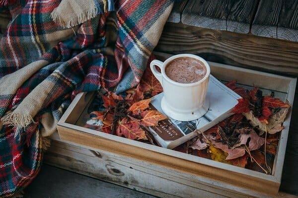 ストール、落ち葉、コーヒーの入ったマグカップ