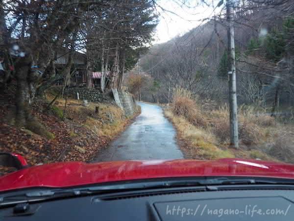 赤い車が細いアスファルト道を走る