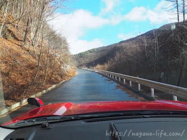 赤い車がアスファルトの道を進む